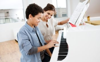 Boy playing piano with teacher