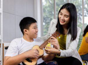 Boy playing Ukulele with teacher